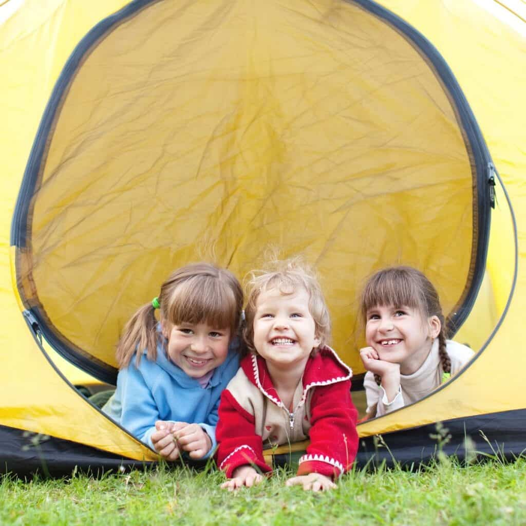 three young children in the doorway of a yellow tent