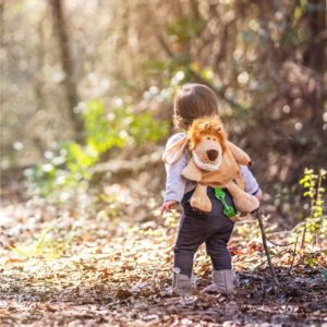 toddler hiking in the forest wearing a lion backpack