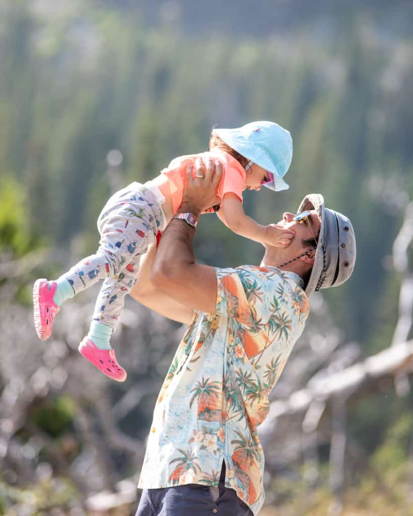 father holding toddler daughter up in the air. Both are wearing hats and sunglasses.