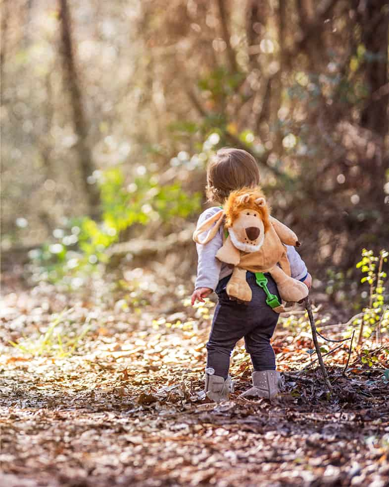 toddler walking on a path in the woods wearing boots and a lion backpack
