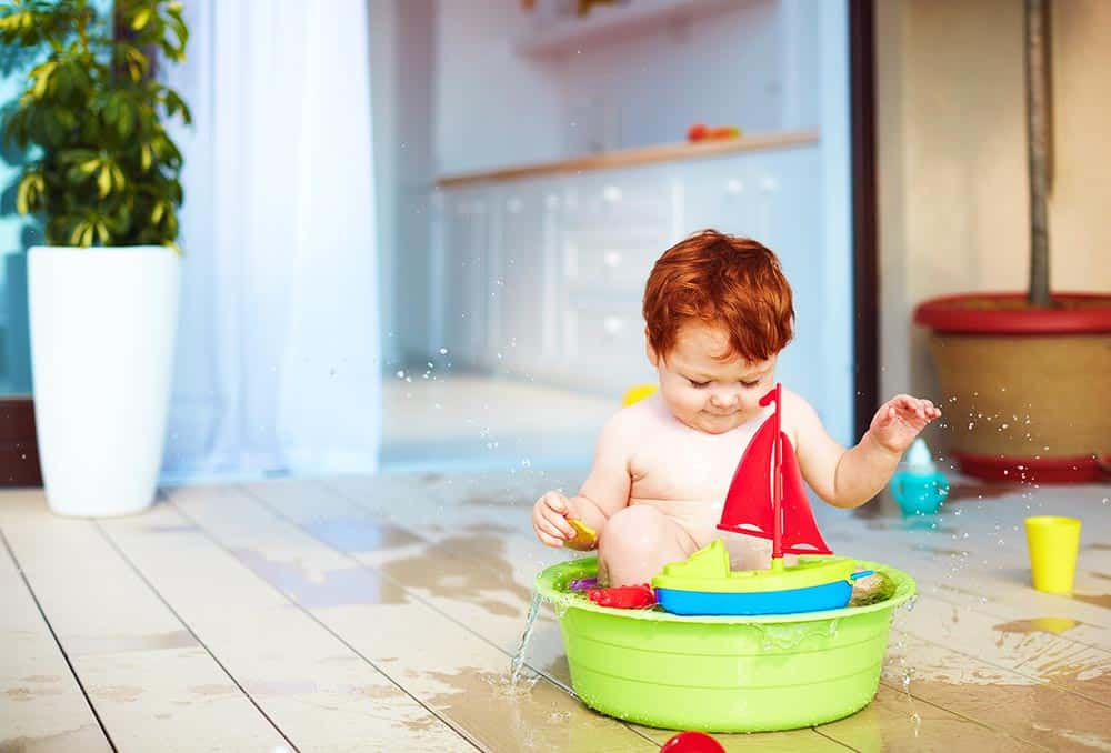 redhead toddler in a green plastic portable tub with a sailboat