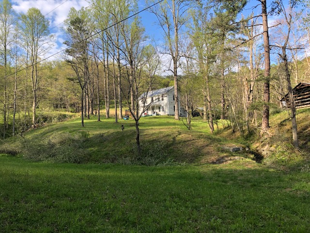 an old white farmhouse on a wooded hill. A log outbidding is visible on the right.