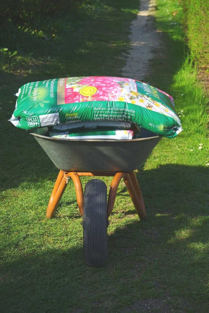 A wheel barrow with two 40 liter bags of potting soil. The wheelbarrow sits at at the end of a gravel bath through grass. The wheel is facing forwards and the handles are invisible behind the stacked potting soil bags.
