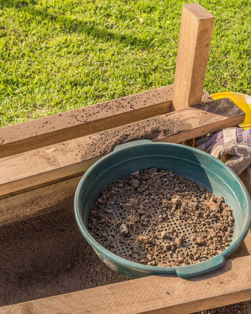 a large green garden sieve with a small amount of dirt in it. the garden sieve is resting on a 2x4 frame and underneath it is a wooden container with sifted soil