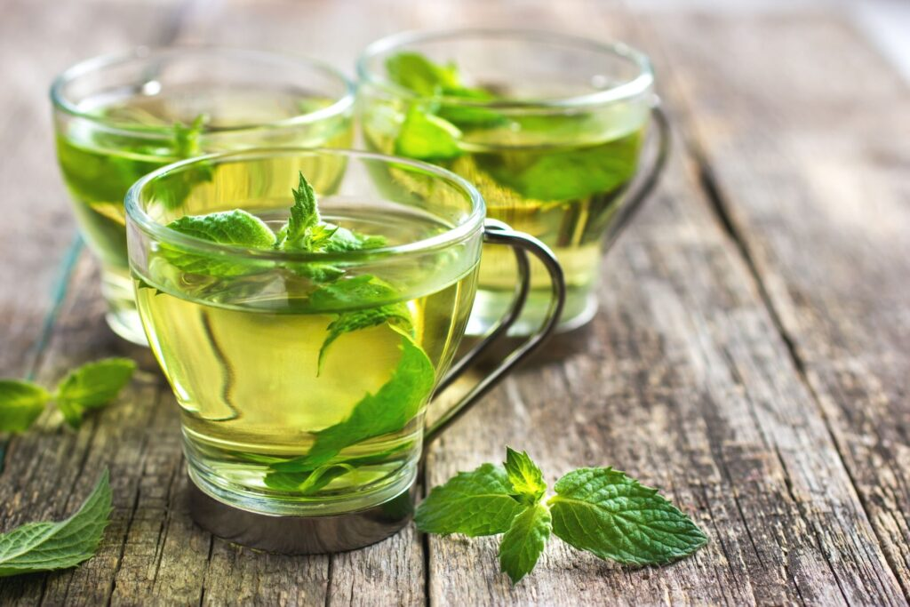 three glass teacups with fresh mint tea on a wood table. There are fresh mint leaves in each cup and on the table.