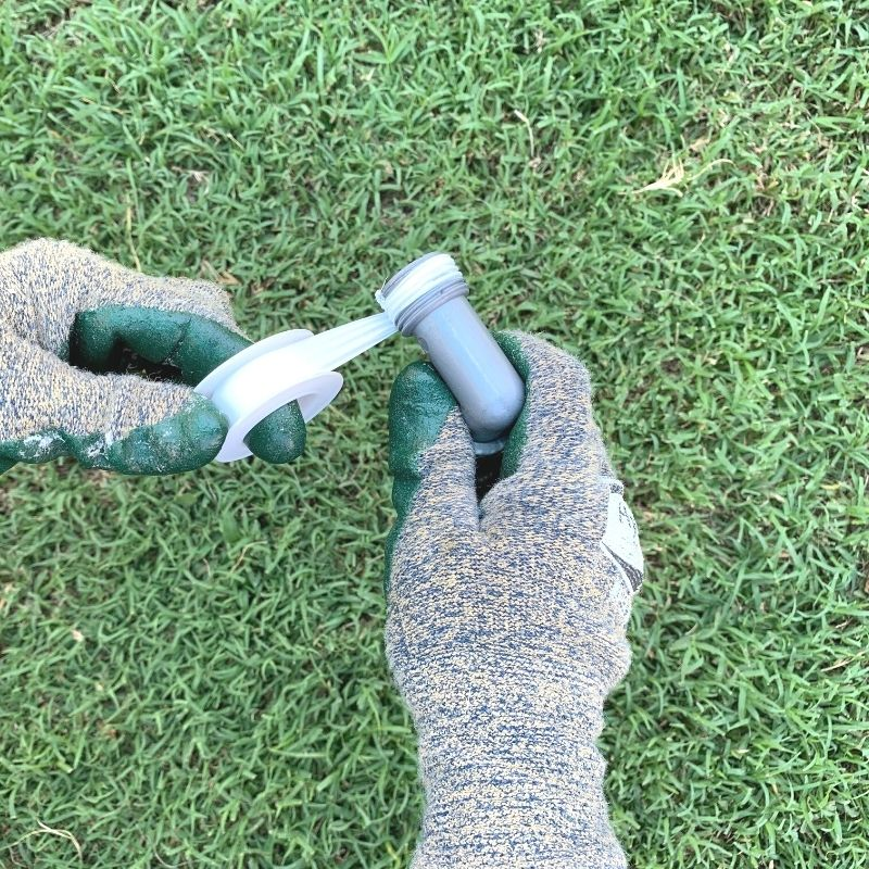 Gloved hands wrapping a male hose reel cart union with plumber's tape. The gloves are green and there is grass in the background