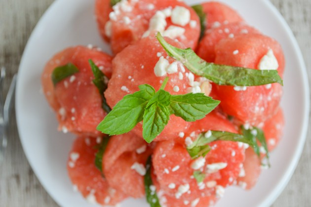 A plate of watermelon chunks with chiffonade mint and feta cheese
