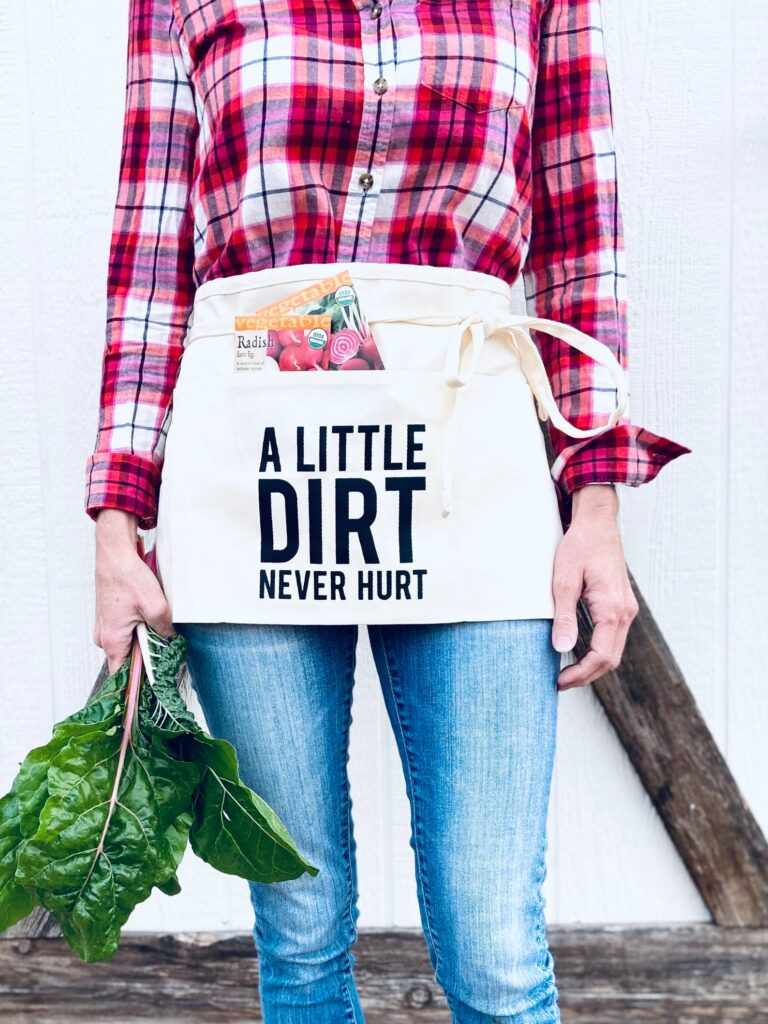 "A woman holding swiss chard and wearing a waist apron with the text ""a little dirt never hurt."" There are radish seed packets sticking out of the apron. She is wearing a red flannel shirt and jeans. The photo shows from her knees to her collar bone - her feet and face are not in the frame."