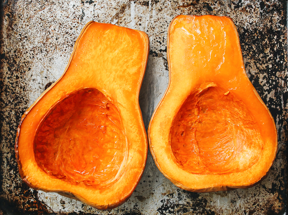 Two cut open and roasted halves of a butternut squash on a baking sheet.
