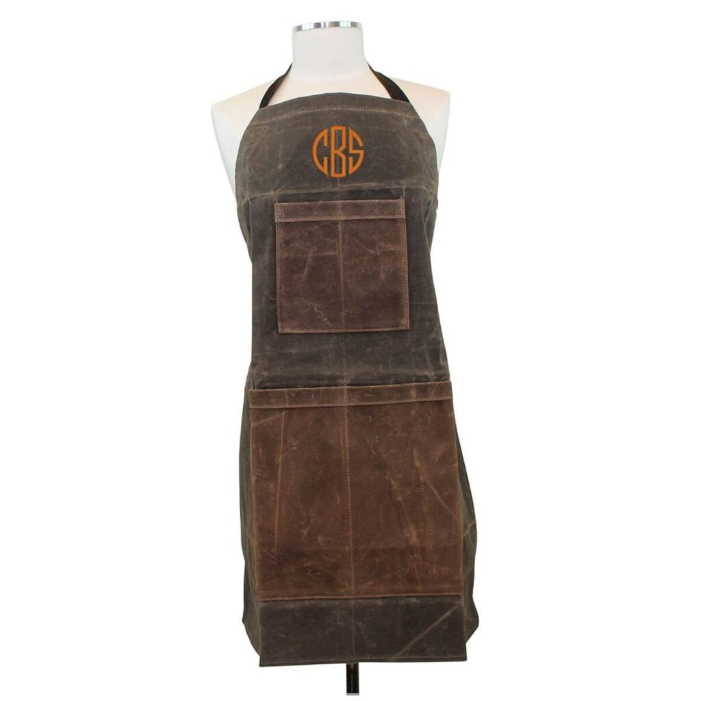 "A long brown waxed canvas apron with an orange monogram ""CBS"" on the chest. The apron is on a plain dress form without a head or arms."