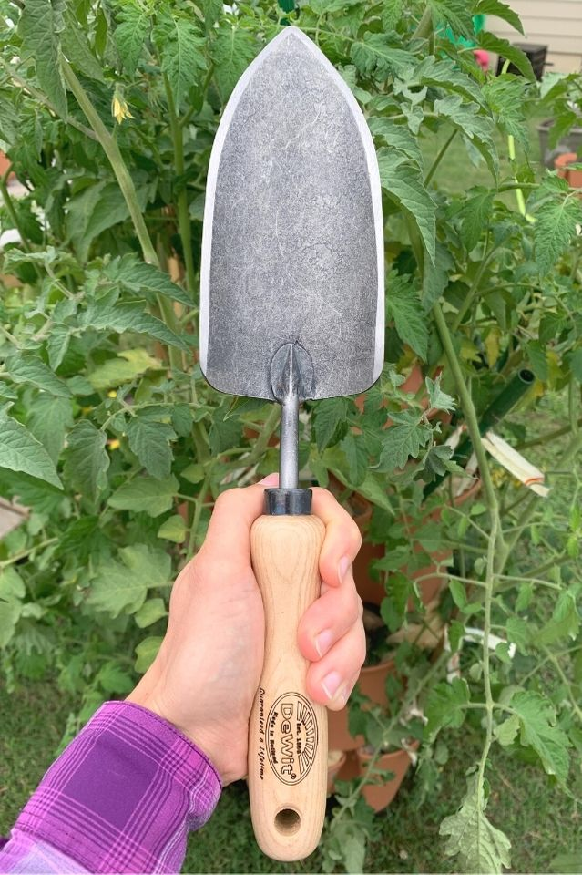 a photo of a woman's hand holding a DeWit brand gardening trowel against a backdrop of tomato plants.
