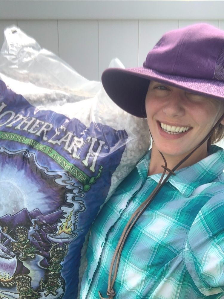A selfie of a woman wearing a teal plaid shirt and a purple gardening hat holding a large bag of perlite