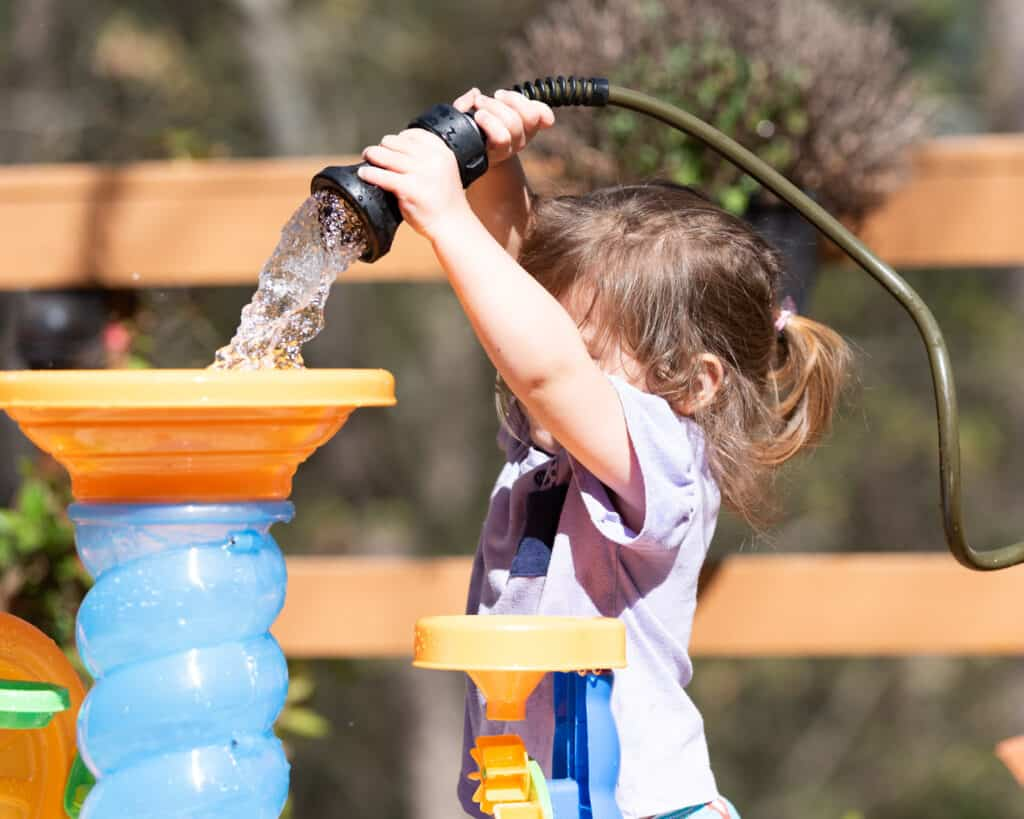 A young child using a fireman hose nozzle to fill a water table