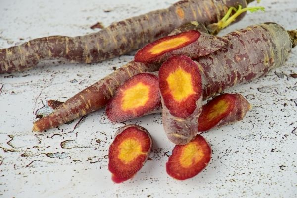 An image of two whole purple carrots and one sliced purple carrot with a yellow center. The carrots on are a weathered white wood surface.