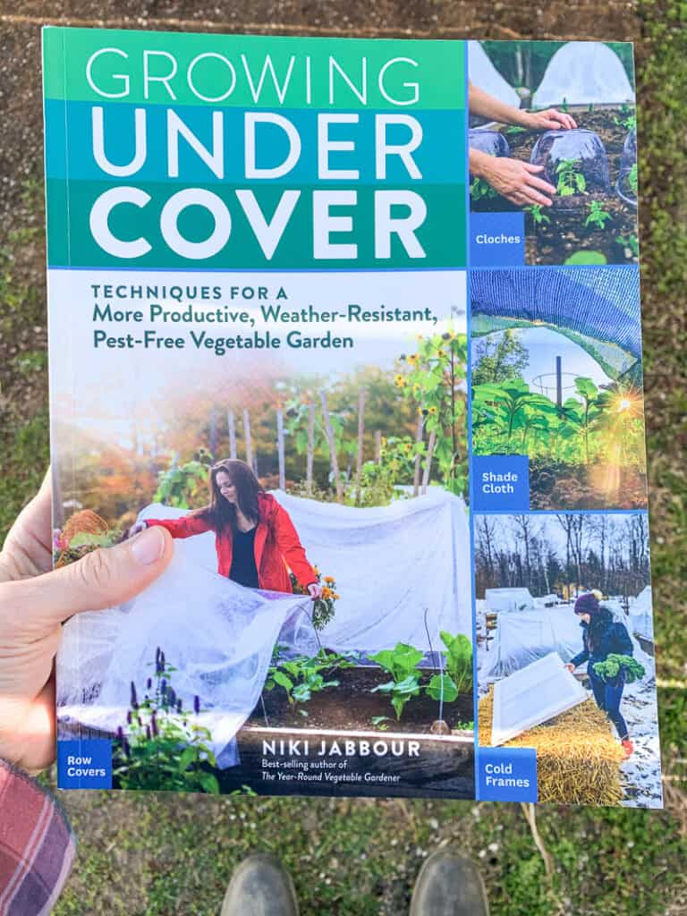 A hand holding the gardening book Growing Under Cover by NIki Jabbour