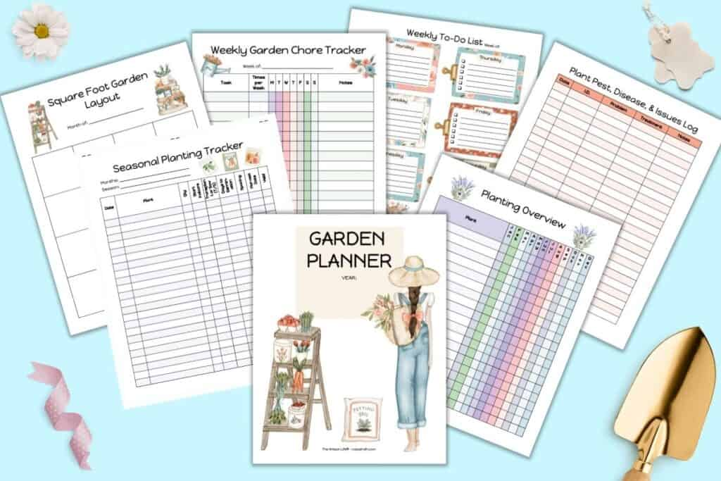 A preview of a printable garden planner pages with colorful, feminine illustrations. The pages are on a blue surface with a gold space, canvas tags, and a daisy flower.