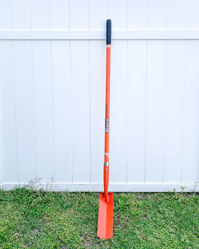 An orange trenching shovel with an orange fiberglass blade leaning against a white vinyl fence