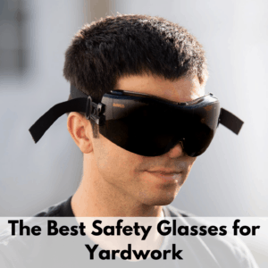 """Text reads, """"The best safety glasses for yardwork."""" Text is on a white transparent text box at the bottom of the image. The photo above is of a man wearing the DeWalt tinted safety goggles. The background is primarily white but is out of focus."""