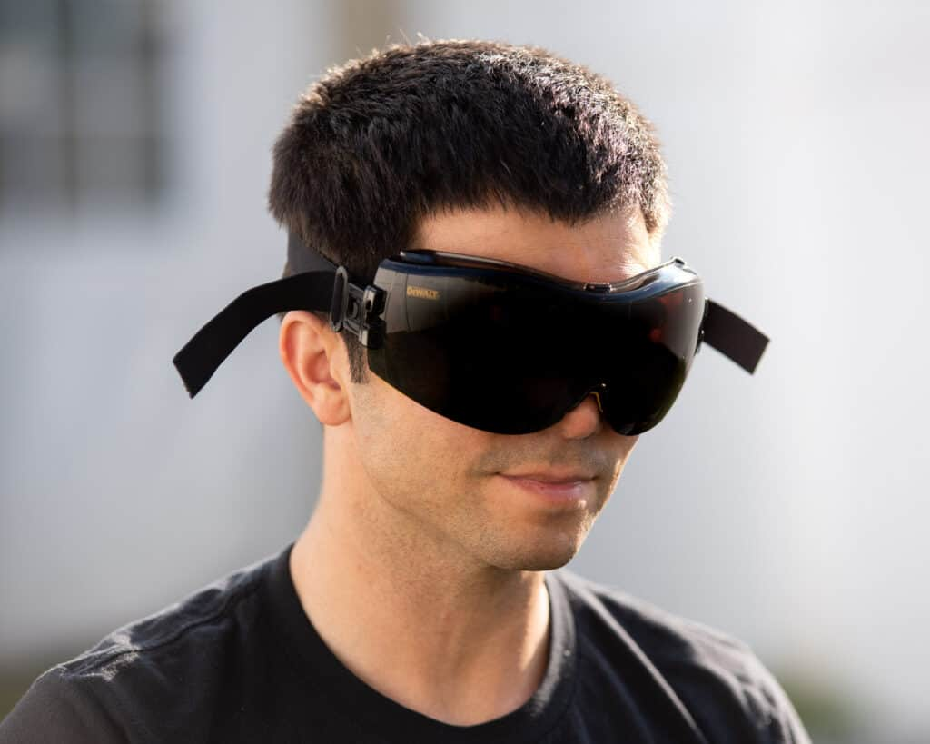 Photo of a man wearing the DeWalt wrap around safety goggles. The background is an out focus white fence.