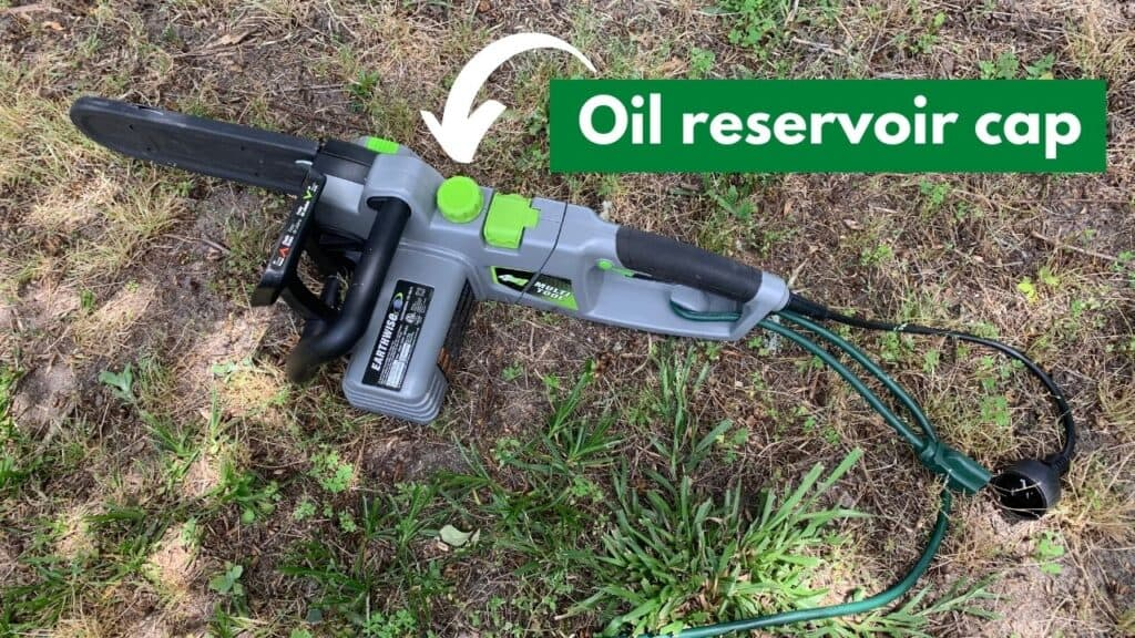 """Text reads """"oil reservoir cap"""" in a green text box with a white arrow pointing to the oil reservoir cap on the earthwise 4 in 1 multi tool chainsaw. The tool is on a grassy patch, sitting on the ground."""