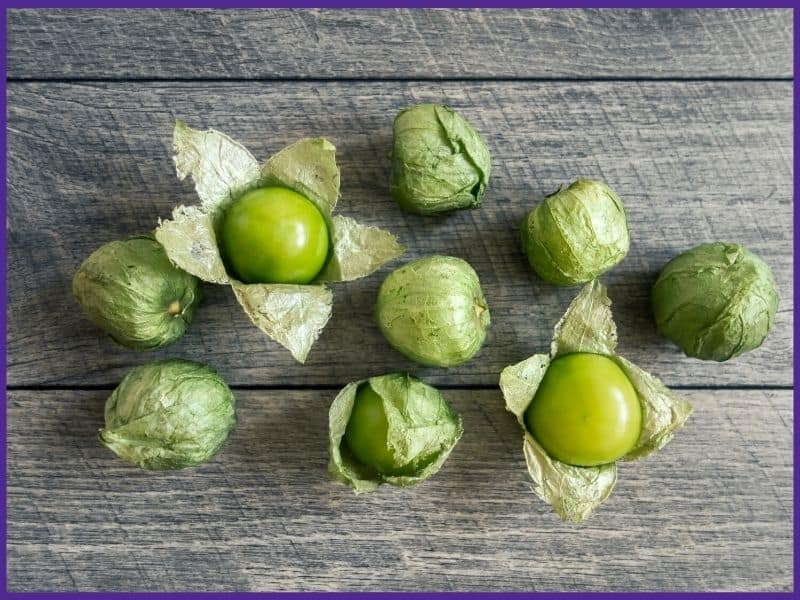 Nine green tomatillos on a wood table