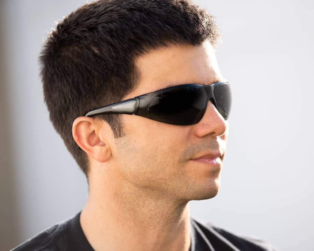Side profile photo of a man wearing basic tinted safety glasses.