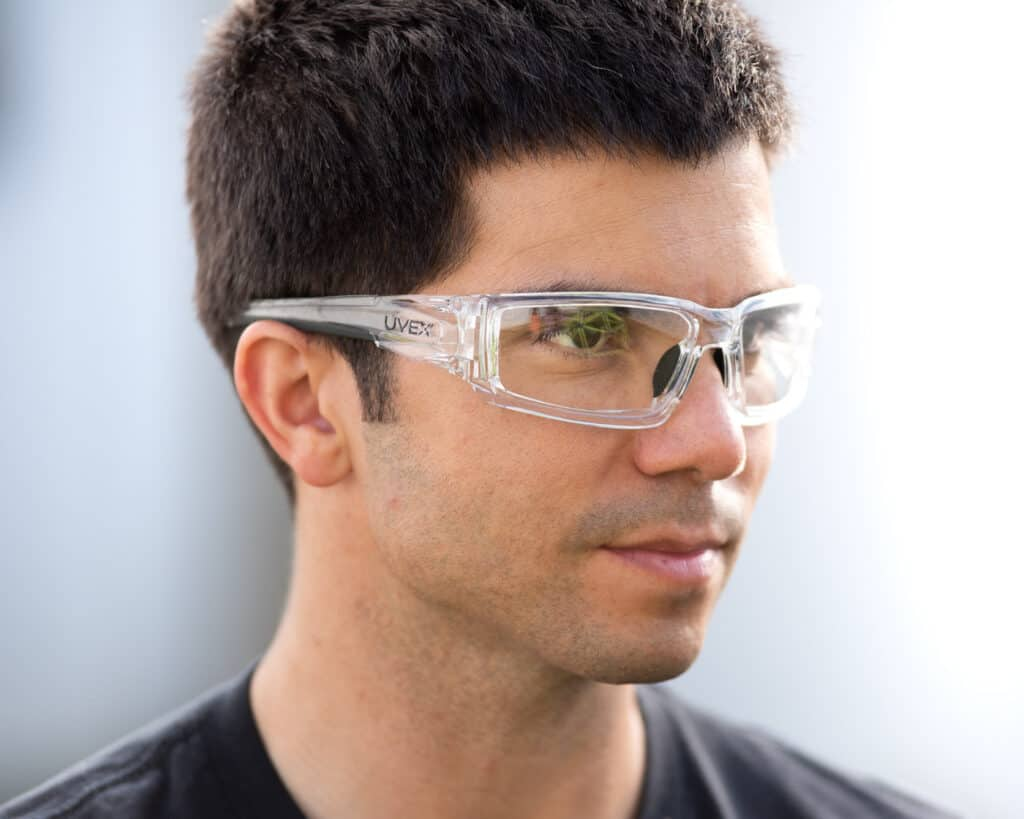 Photo of a man wearing the clear UVEX safety glasses looking away from the camera. Background is an out of focus white fence.