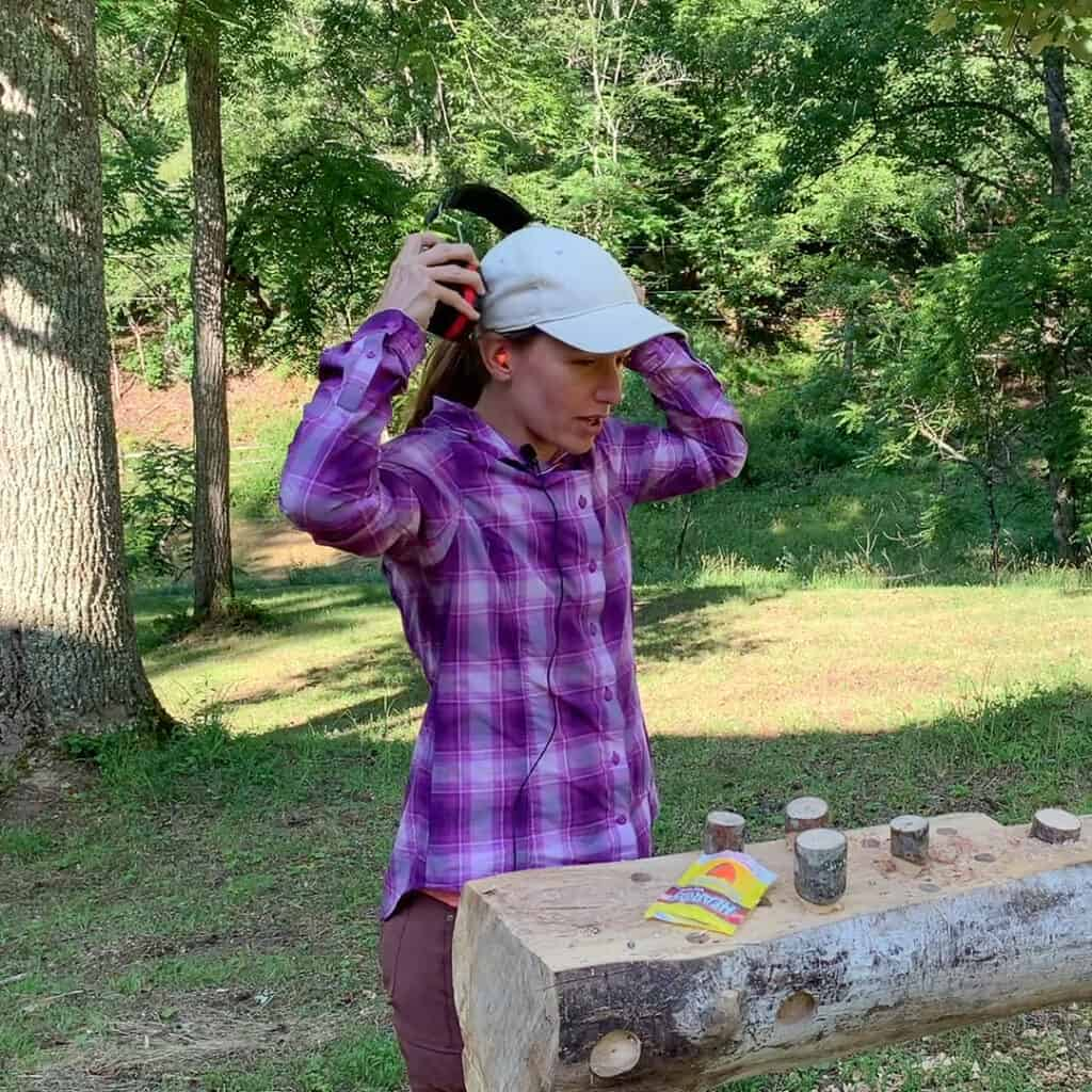 Photo is of a woman placing a set of earmuffs over a set of earplugs and showing how to wear double hearing protection. The woman is a wearing a purple plaid shirt, red pants, and a white hat. The background is of a wooded lot.