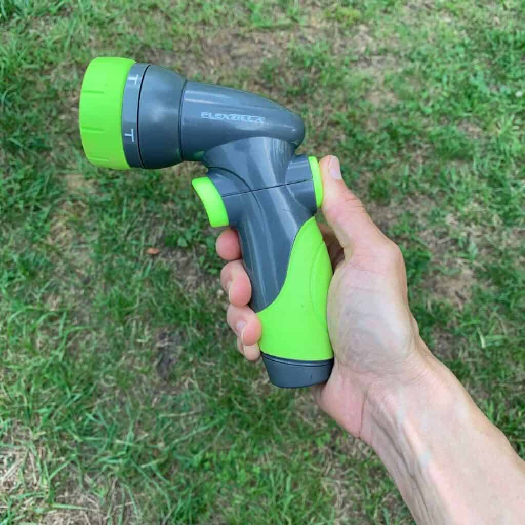 A woman's hand holding a grey and chartreuse green Flexzilla pattern hose nozzle