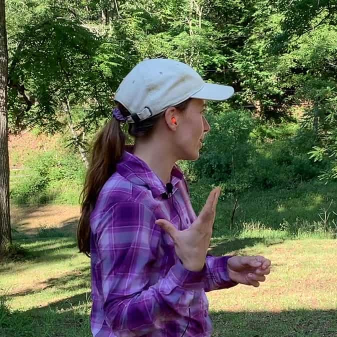 Photo is of a side profile of a woman wearing orange earplugs. She is wearing a purple plaid shirt and a white hat. The background is a forested lot.
