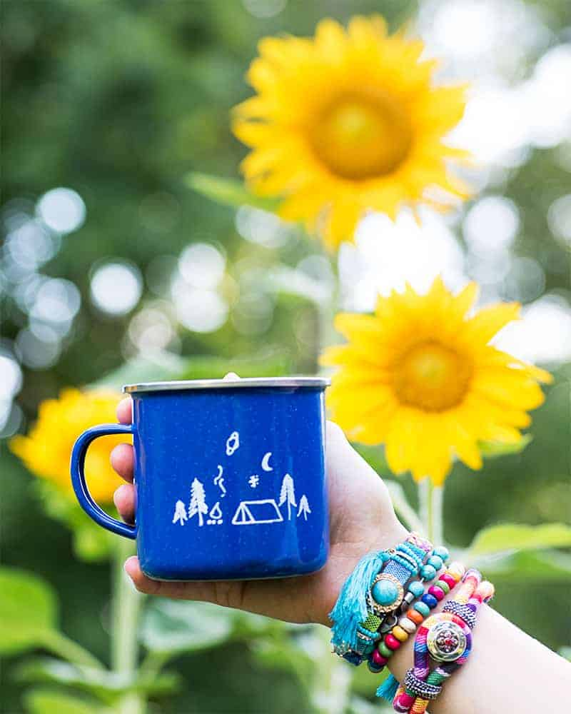 A hand holding a blue camp mug in front of a garden patch with blooming sunflowers