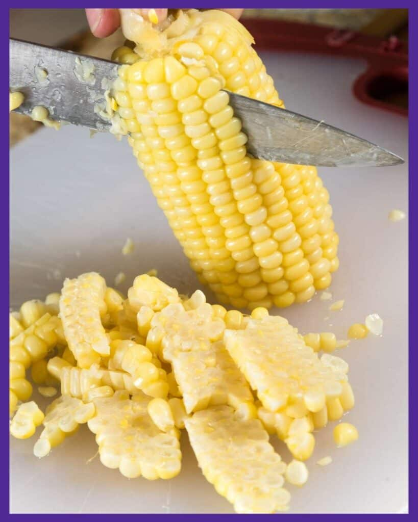 A close up image of a person cutting corn off the cob with a large knife