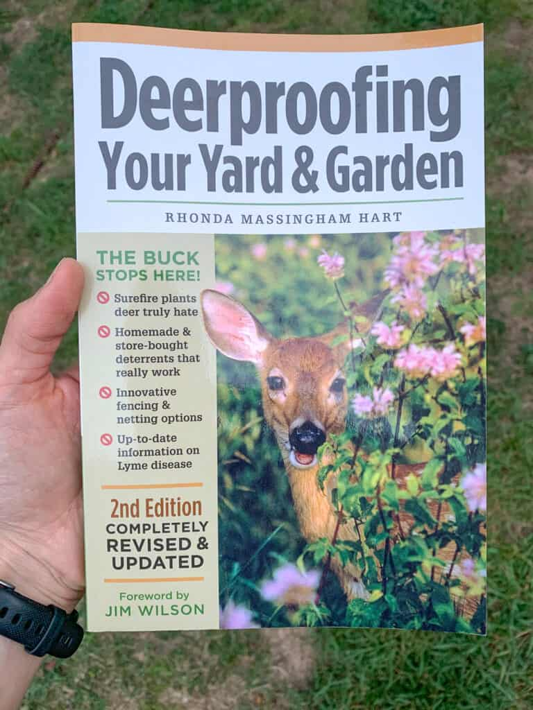 A hand holding the book Deerproofing Your Yard and Garden by Rhonda Massingham Hart