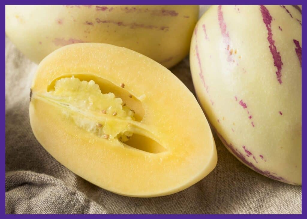 A cut open pepino melon. It has a yellow skin with purple stripes. The inside has yellow flesh.